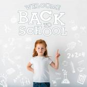 aranyos vörös hajú gyerek néz kamera és ujjal mutogatás közel üdvözlendő vissza az iskolai levelek fehér