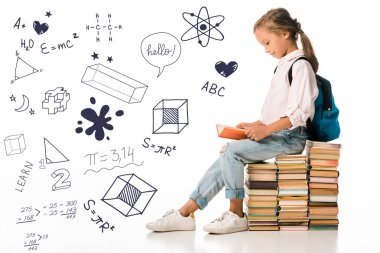 cheerful schoolkid sitting on books and reading near letters and mathematical formulas  on white