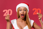 Photo excited african american girl in santa hat and christmas dress holding 2020 paper cut number isolated on red