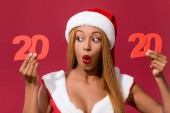 shocked african american girl in santa hat and christmas dress holding 2020 paper cut number isolated on red
