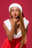 szexi afro-amerikai lány télapó kalap és karácsonyi ruha mutatja csend gesztus elszigetelt piros