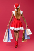 vissza kilátás fiatal afro-amerikai lány télapó kalap és karácsonyi ruha séta bevásárlótáskák piros háttér