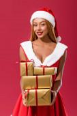 szexi afro-amerikai lány télapó kalap és karácsonyi ruha gazdaság ajándék dobozok elszigetelt piros