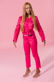 attractive, trendy african american woman standing on pink background, fashion doll concept