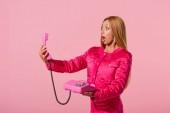schockierte, modische afrikanisch-amerikanische Frau schaut auf Handy isoliert auf rosa, Modepuppenkonzept