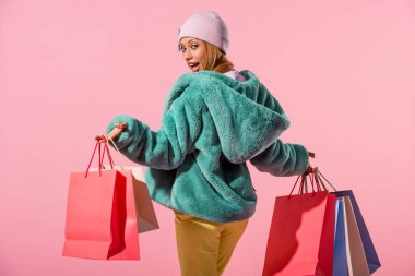 smiling, fashionable african american woman smiling at camera while holding shopping bags on pink background, fashion doll concept