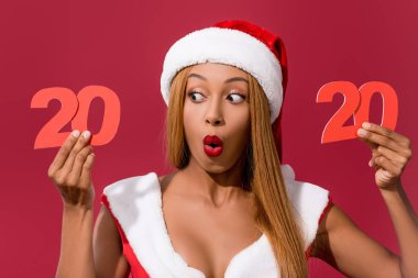 Shocked african american girl in santa hat and christmas dress holding 2020 paper cut number isolated on red stock vector