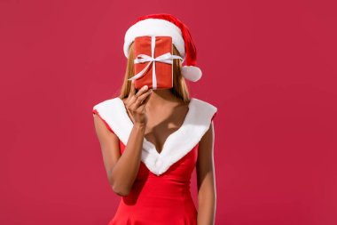 young african american girl in santa hat and christmas dress hiding face behind gift box isolated on red