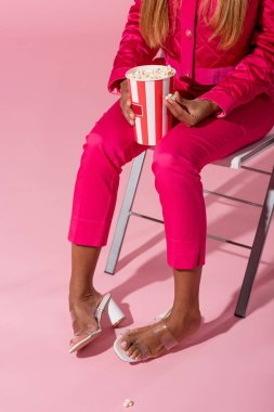 Cropped view of stylsh african american woman sitting on chair with cup of popcorn on pink background, fashion doll concept stock vector