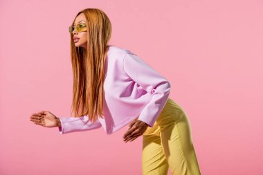 stylish, blonde african american woman stepping isolated on pink, fashion doll concept