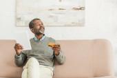 älterer afrikanisch-amerikanischer Mann mit digitalem Tablet und Kreditkarte, während er auf dem Sofa sitzt und wegschaut