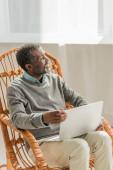 fröhlicher afrikanisch-amerikanischer Mann sitzt im Korbstuhl mit Notizbuch und schaut weg