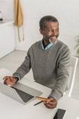 veselý africký Američan dívá pryč, zatímco sedí v blízkosti notebooku a drží kreditní kartu