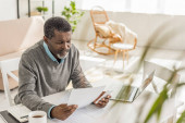 selective focus of senior african american man looking at utility bill while sitting near laptop