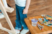 cropped view of child standing near wooden table with gouache paints