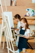 cute kids holding palette and painting in art school