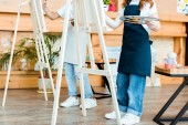cropped view of kids in aprons standing near easels