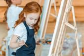 selective focus of cute kid standing and painting in art school