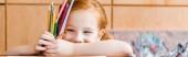 panoráma lövés mosolygós vörös hajú gyermek kezében színes ceruzák