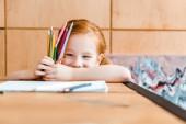 szelektív fókusz mosolygós vörös hajú gyermek kezében színes ceruzák