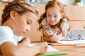 selective focus of cute redhead kid looking at adorable child drawing on paper