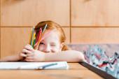 szelektív fókusz aranyos vörös hajú gyerek kacsintás szem, miközben a kezében színes ceruzák