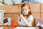 roztomilý ryšavý kluk drží barevné tužky v umělecké škole