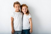 cheerful kids hugging while standing on white