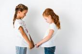 Fotografie boční pohled na veselé děti s barvou na trička stojící na bílém