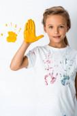 roztomilé dítě ukazující žlutou barvu na ruce v blízkosti žluté ruční tisk na bílém