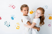 Fotografie happy kids hugging near hand prints on white