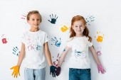 happy children with paint on hands standing near colorful hand prints on white