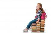 Photo surprised redhead schoolkid sitting on books on white