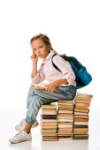 Photo adorable schoolkid sitting on books and looking at camera on white