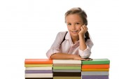 cheerful pupil smiling while looking at camera near colorful books isolated on white