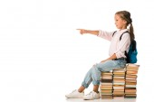 Photo cheerful kid sitting on books and pointing with finger on white