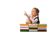 pozitivní školák ukazuje prstem při pohledu pryč v blízkosti barevné knihy izolované na bílém