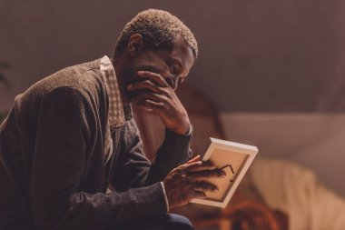 senior, depressed african american man looking at photo frame