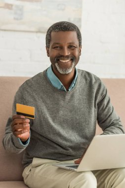 Senior african american man sitting on sofa with laptop, holding credit card and smiling at camera stock vector