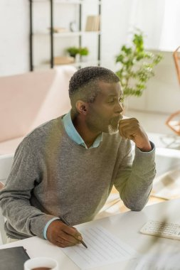 thoughtful african american man sitting at table near utility bill and looking away
