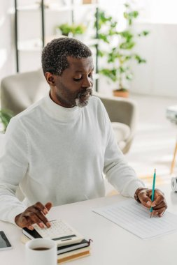 attentive african american man sitting at table and calculating communal expenses