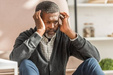 upset african american man sitting on floor and holding hands near head while suffering from migraine