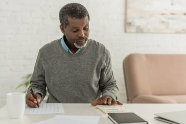 concentrated african american man calculating expenses while writing in utility bill