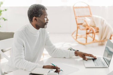 serious african american man using laptop while calculating communal expenses