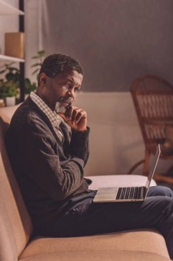 upset african american man sitting on sofa with laptop at night