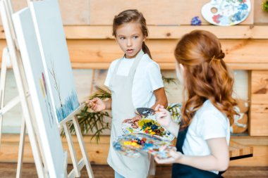selective focus of adorable kid looking at redhead child near easels in art school