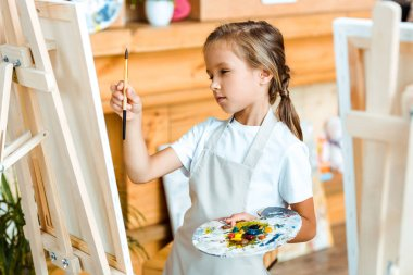 Selective focus of serious child painting in art school stock vector