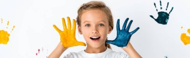 Panoramic shot of excited kid with paint on hands near hand prints on white stock vector