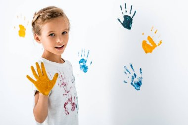 Happy kid with yellow paint on hand near hand prints on white stock vector