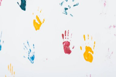 Selective focus of yellow, blue and red hand prints on white stock vector
